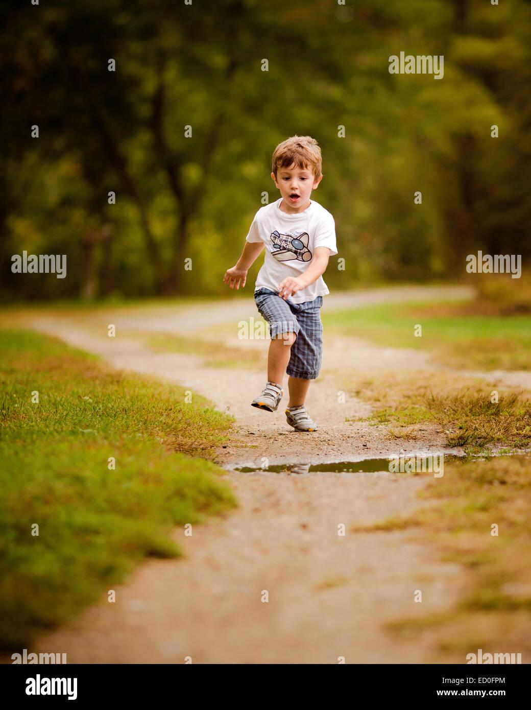 Junge läuft auf Fußweg etwa, über eine Pfütze zu springen Stockbild
