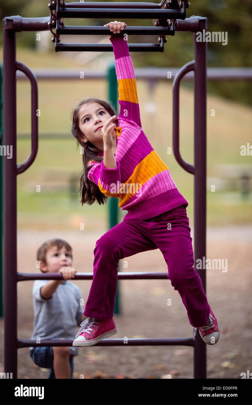 Mädchen und Jungen spielen auf Klettergerüst Stockbild