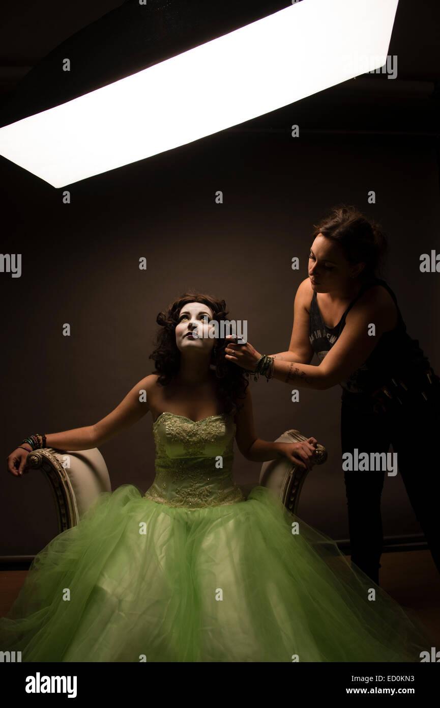 Fantasy-Makeover-Fotografie: eine junge Frau-Mädchen-Modell gebildet durch eine Visagistin auszusehen wie ein White-faced Porzellan gemalt, Puppen- und posiert wie eine Puppe in einem Fotostudio tragen eine große grüne Kleid Kleid Ballkleid Stockfoto