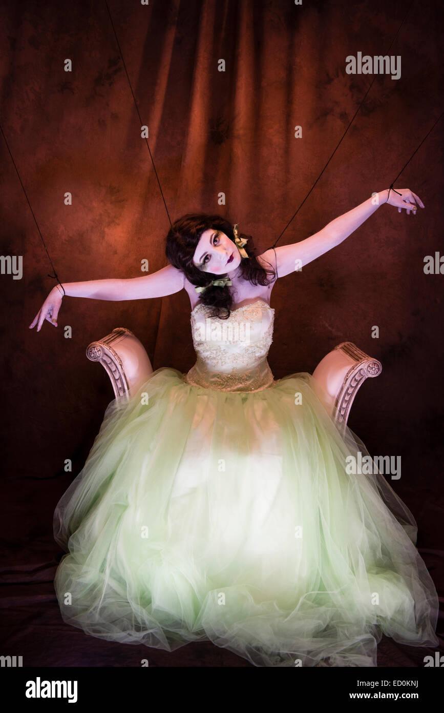Fantasy-Makeover-Fotografie: eine junge Frau-Mädchen-Modell gebildet um zu schauen wie White-faced bemalte Puppe Porzellan und posiert wie eine Puppe in einem Fotostudio tragen eine große grüne Kleid Kleid Ballkleid Stockfoto