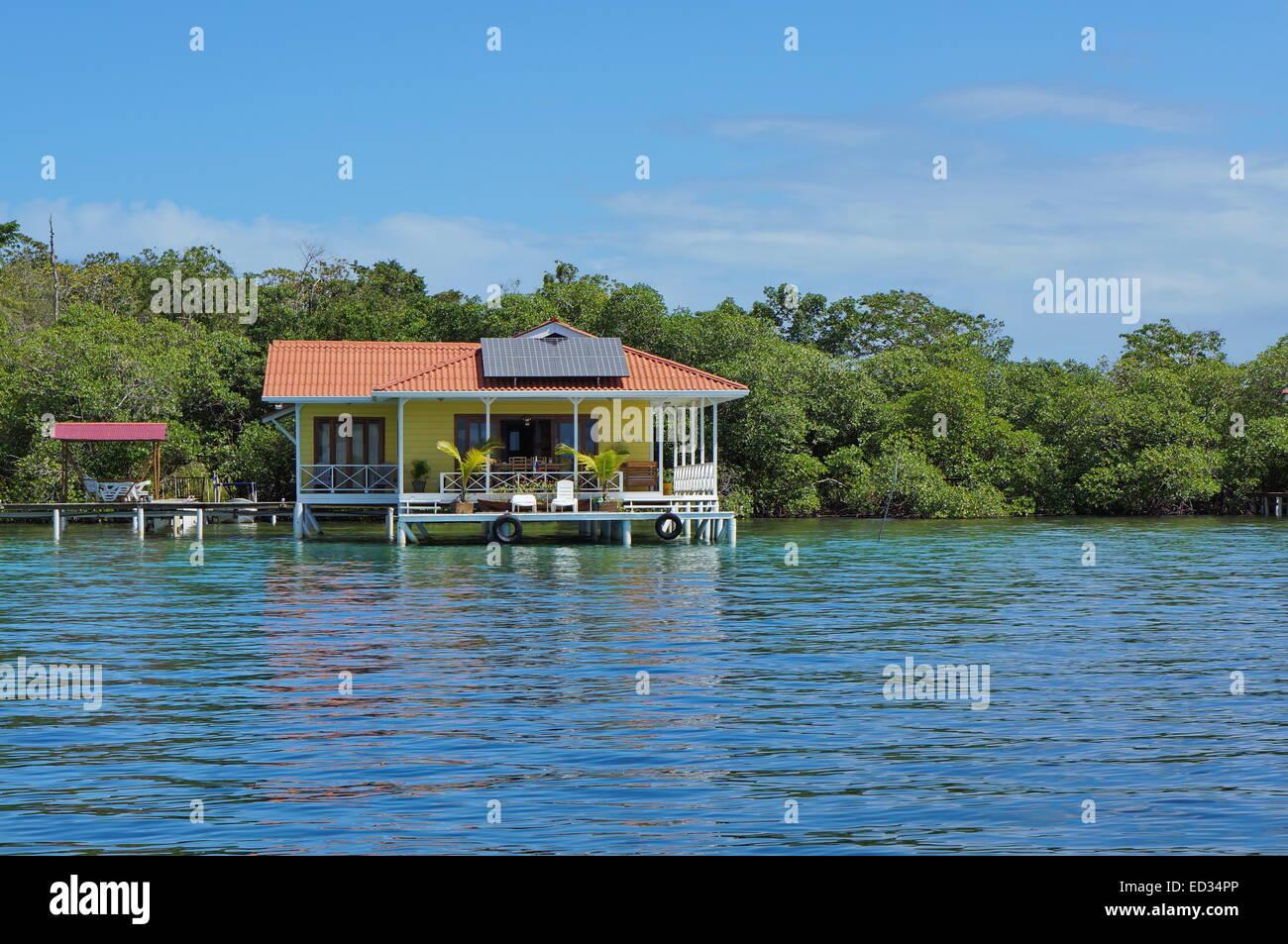 Off Grid Haus oberhalb des Meeres mit Sonnenkollektoren auf dem Dach, Karibik, Panama Stockbild
