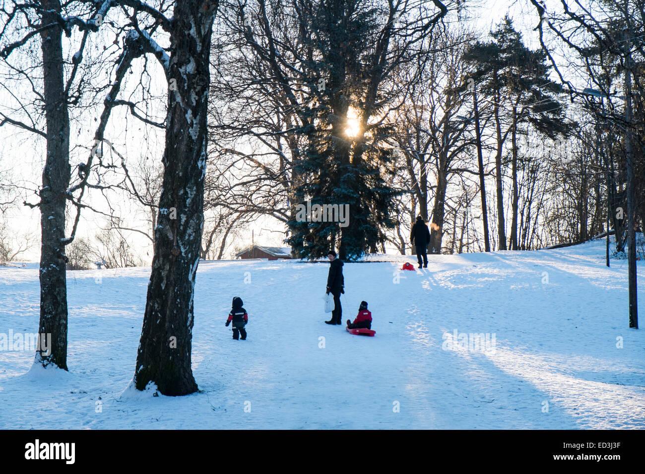 Familie spielt im Schnee in Oslo Norwegen. Tiefstehende Sonne Stockbild