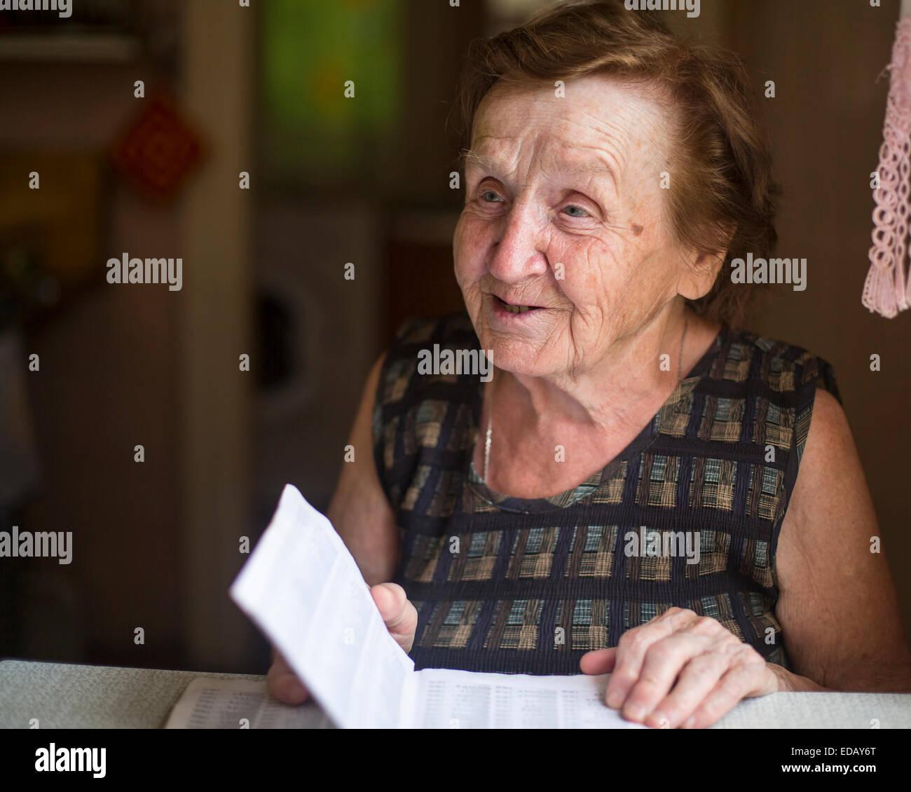 Alte Frau emotional spricht und liest in einem Notebook in seinem Haus. Stockbild