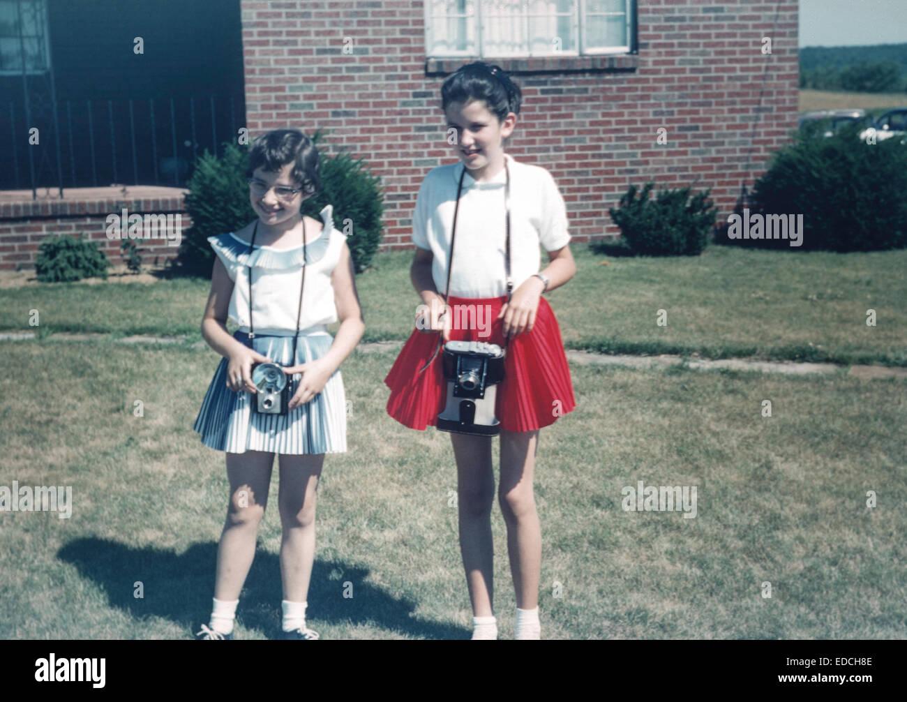 Vintage Bild von zwei jungen Mädchen posiert mit Kameras, 50er Jahre Stockbild