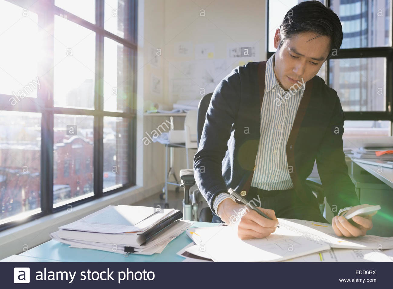 Architekten entwerfen Pläne im sonnigen Büro Stockbild
