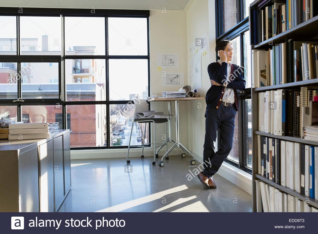 Geschäftsmann am Handy am Bürofenster sprechen Stockbild