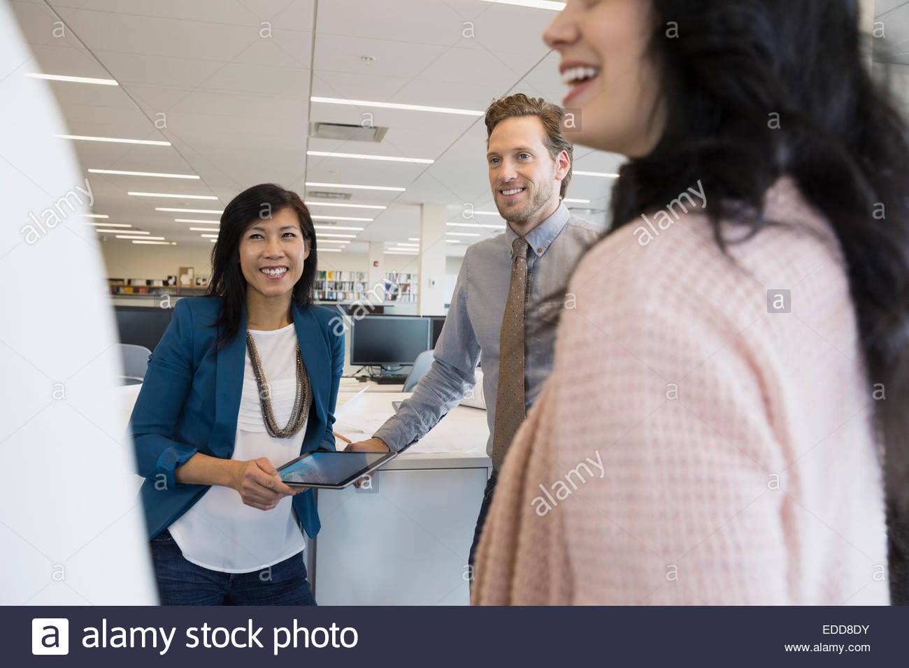 Lächelnde Geschäftsleute sprechen im Kreis Stockbild