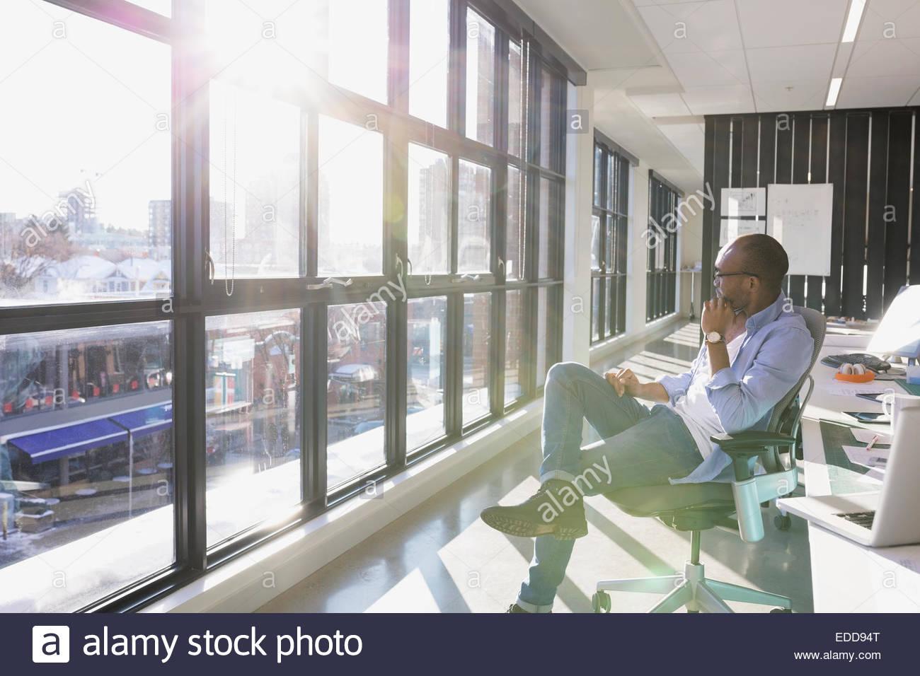 Nachdenklich Geschäftsmann sonnigen Bürofenster mit Blick Stockbild