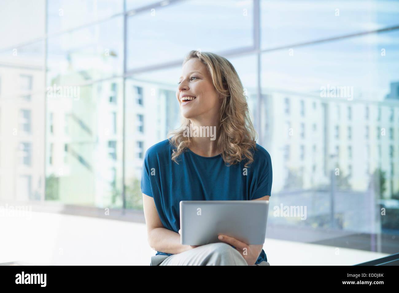 Reife Frau lächelnd mit digital-Tablette in ihrer Wohnung sitzt Stockbild