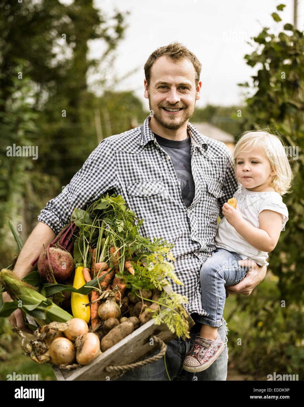 Mann in seiner Zuteilung mit seiner Tochter, Lächeln, halten eine Kiste voller frisch geerntete Gemüse. Stockbild