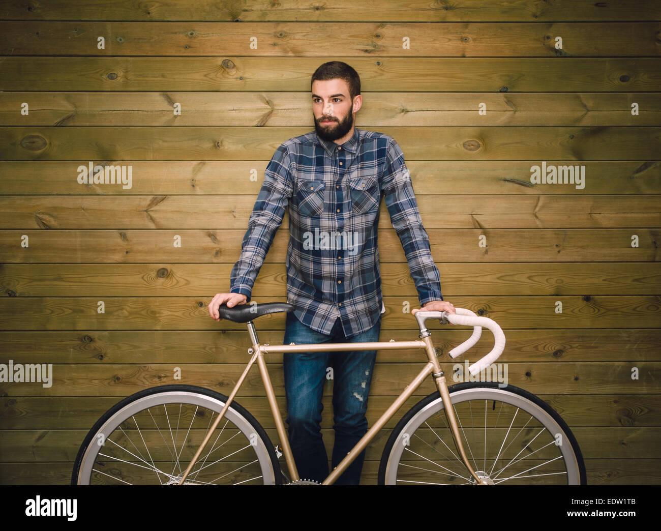 Hipster-Mann mit seinem Fixie-Bike auf einem hölzernen Hintergrund Stockbild