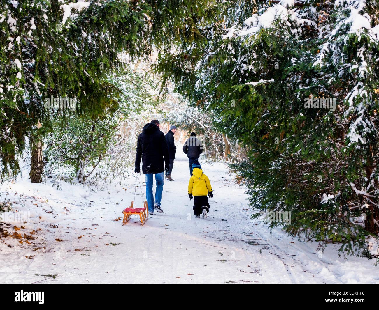 Mann mit Kind und Rodel zu Fuß nach schweren Winterschnee im öffentlichen Park, Humbolthain Volkspark Stockbild