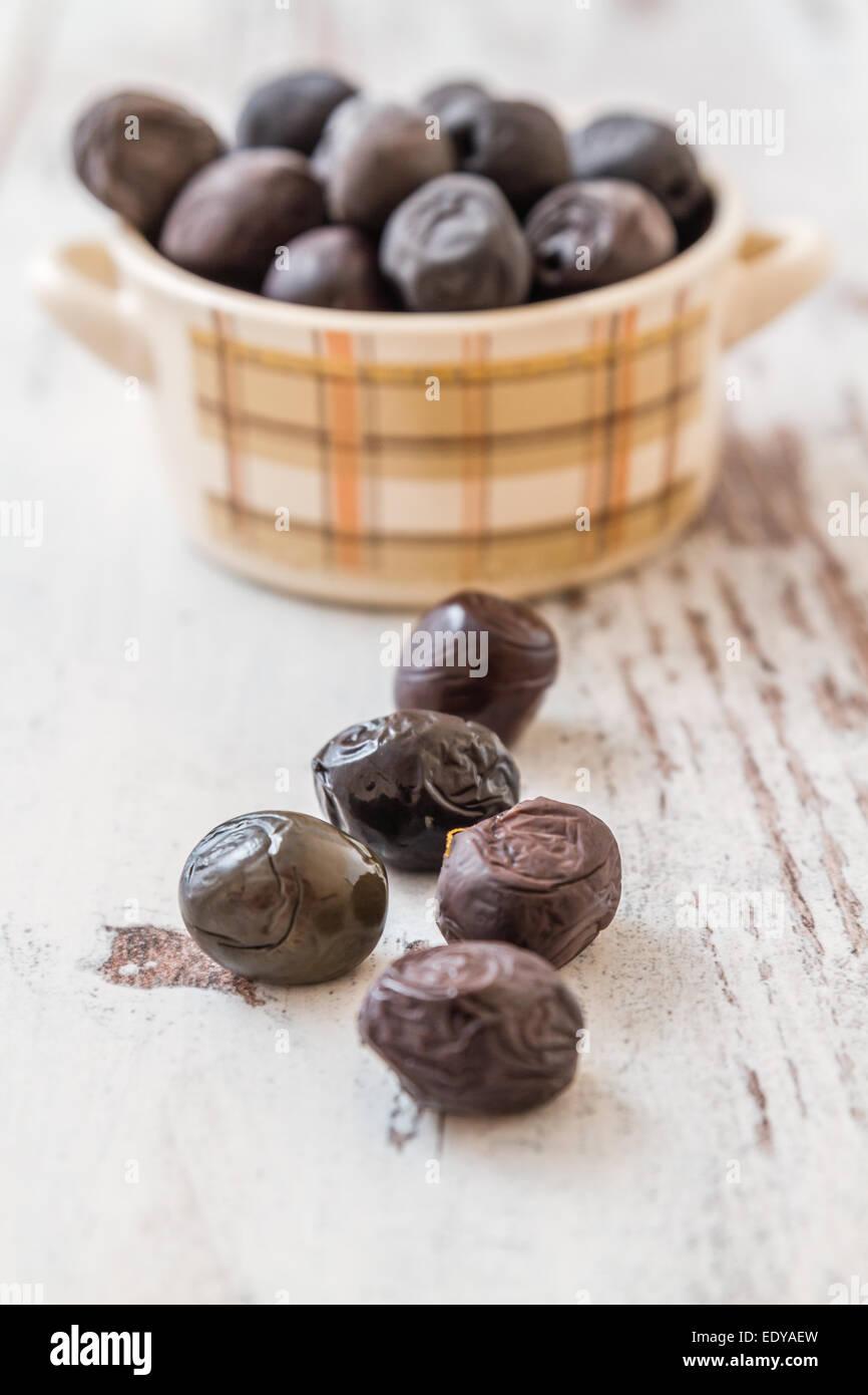 Schwarze Oliven in kleine Küchenutensil auf weißem Holz Hintergrund Stockbild