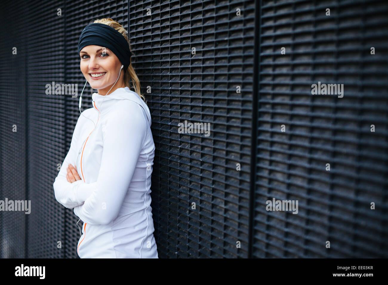 Porträt von schöne junge Frau in Sportkleidung, Blick auf die Kamera zu Lächeln. Sportliche Frau, die an eine Wand Stockfoto