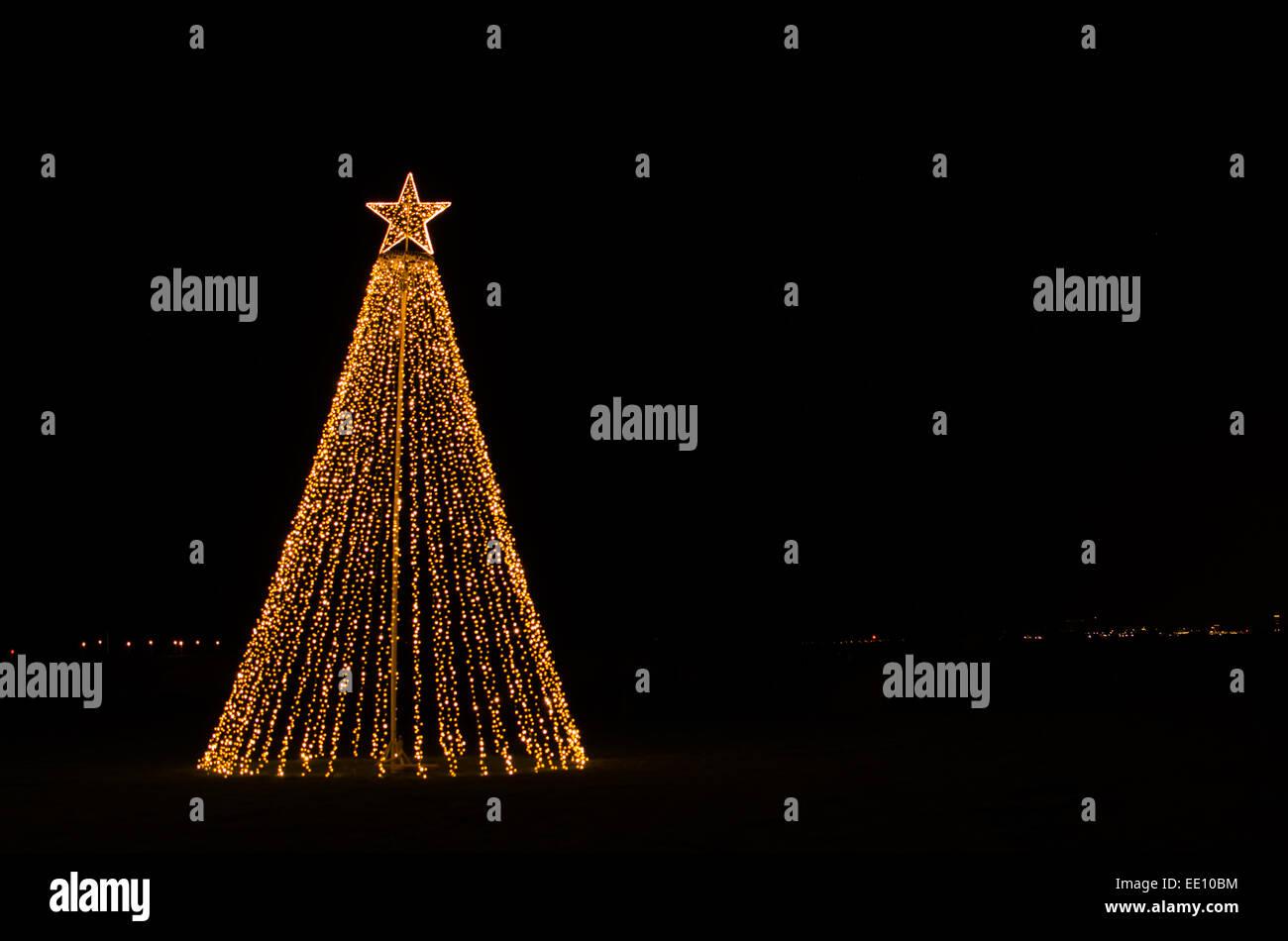 Outdoor-Weihnachtsbeleuchtung in Form eines Weihnachtsbaumes mit einem Stern auf der Spitze Stockbild