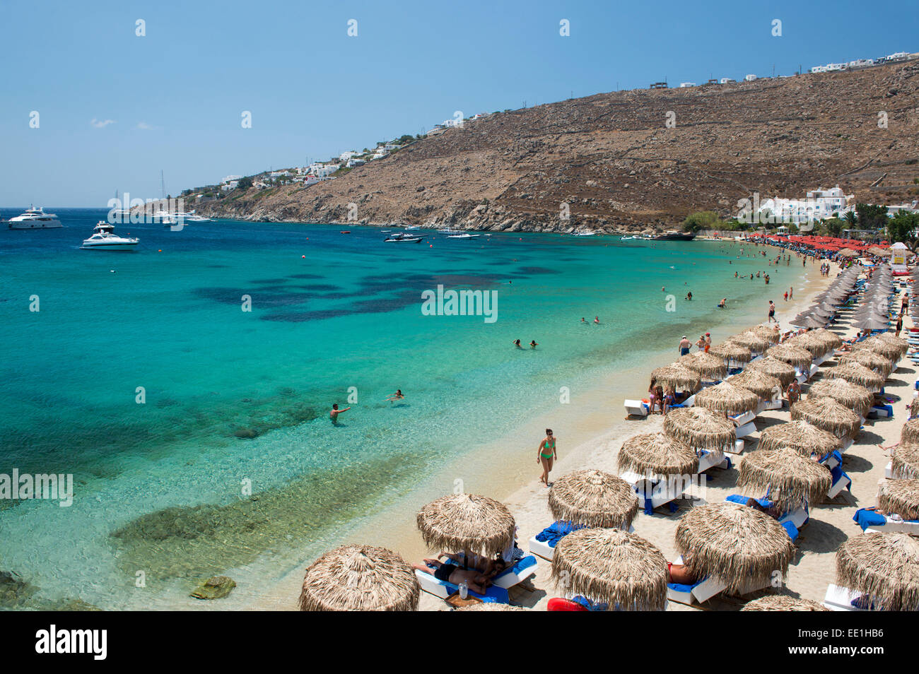 Strohgedeckte Sonnenschirme am Strand von Ornos auf Mykonos, die Kykladen, griechische Inseln, Griechenland, Europa Stockbild