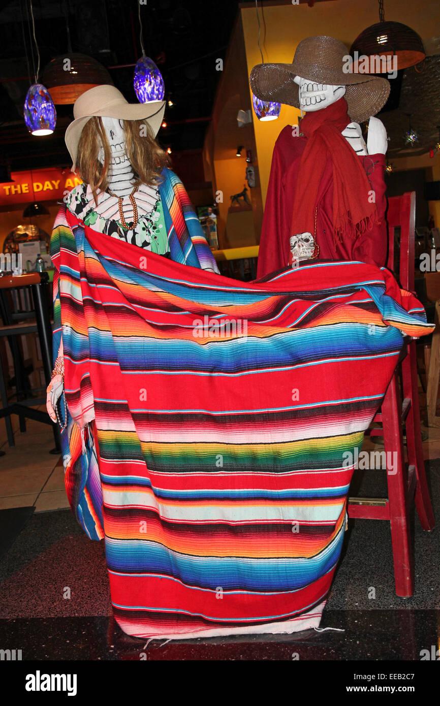 Skelette, die Feiern zum Dia De Los Muertos eingewickelt In bunt gestreifte Decke In einer Tequila-Bar, Miami Flughafen Stockbild