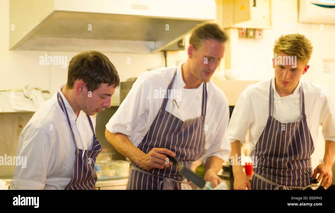 Köche und Küchenpersonal arbeiten in einer belebten Küche Stockbild