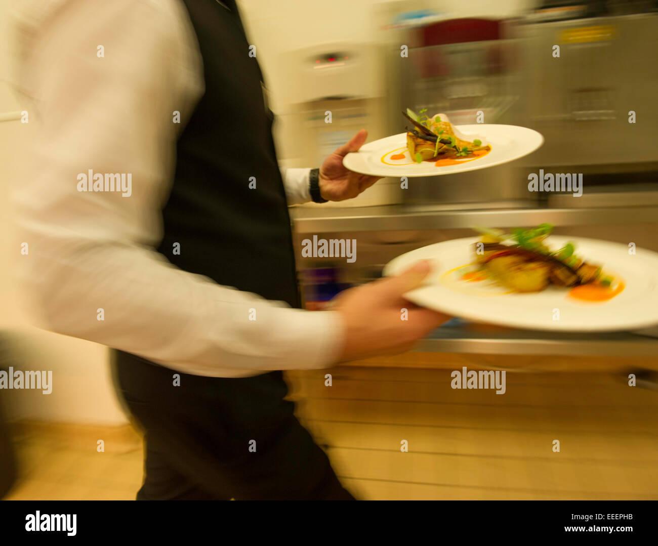 Eine Kellnerin, die Essen aus der Küche bringen Stockbild