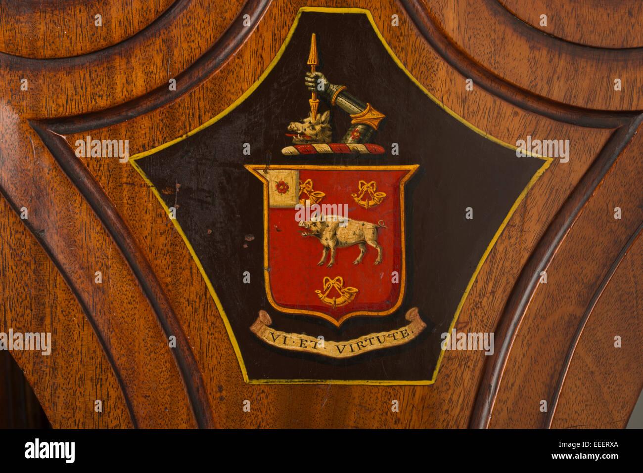Familienwappen gemalt auf einem Holzstuhl. Motto des Vi et Virtute (durch Stärke und Tapferkeit) ein Schild Stockbild