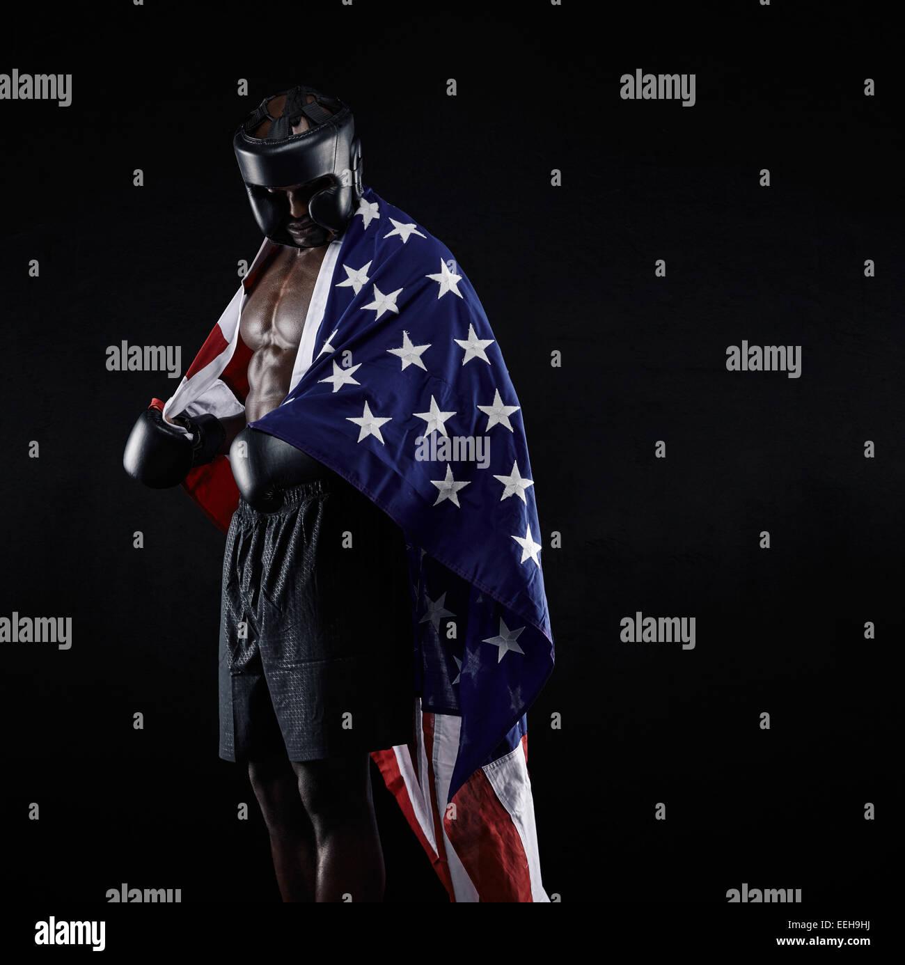Porträt des afroamerikanischen Boxer mit der amerikanischen Flagge drapiert um seinen Körper vor schwarzem Stockbild