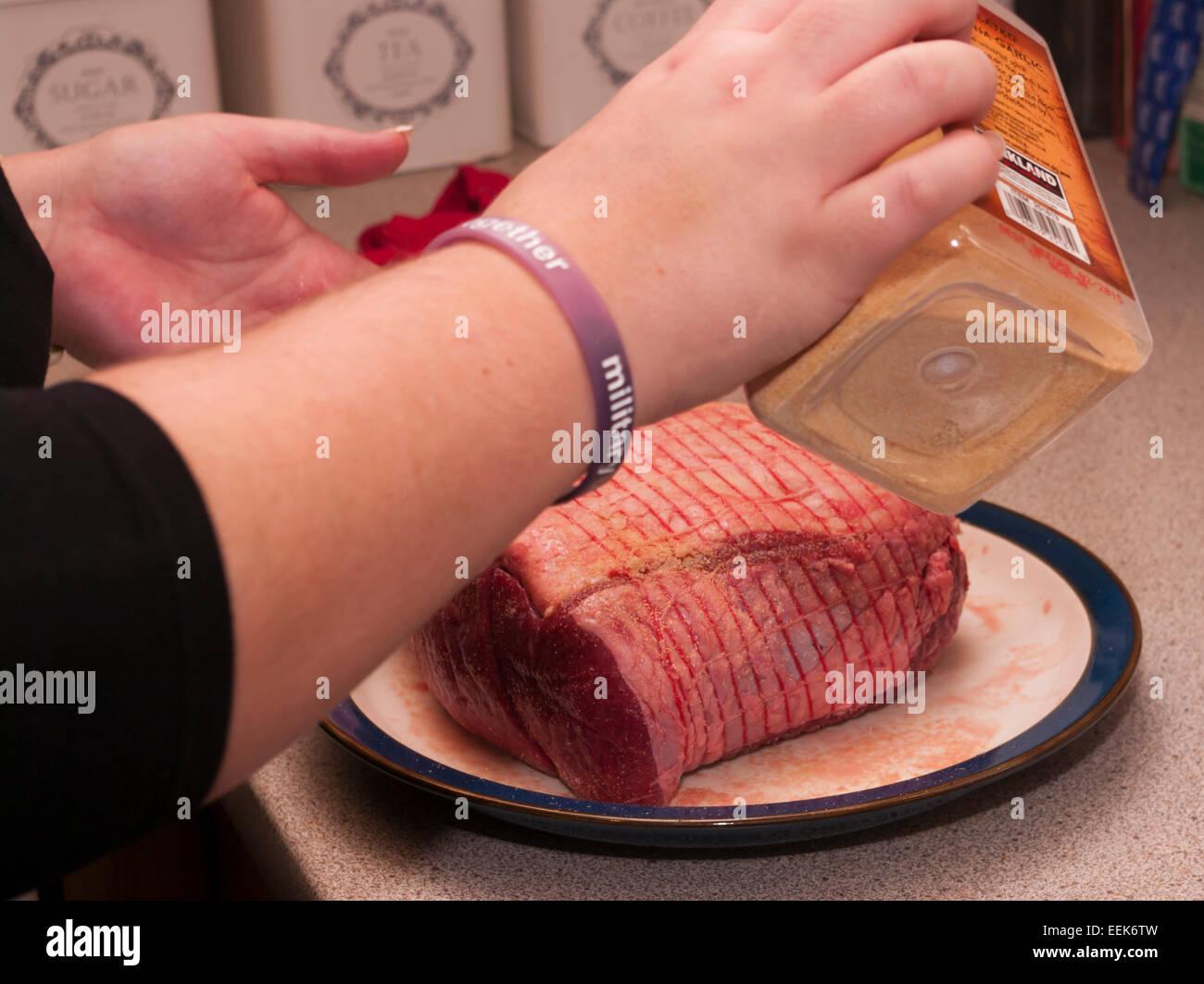 Frau eine Fuge von Rindfleisch würzen Stockbild
