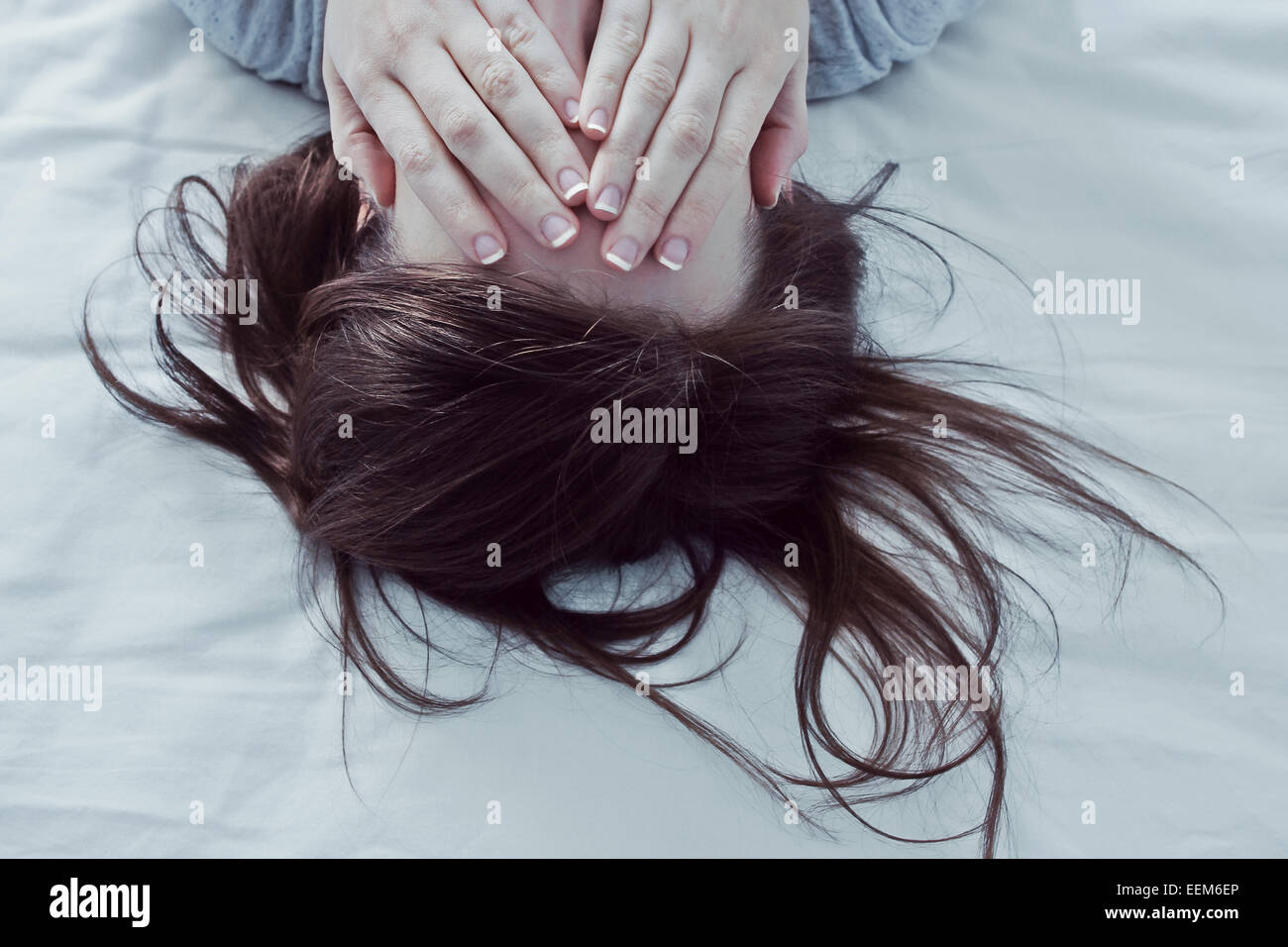 Frau auf Bett für ihre Augen mit Händen Stockbild