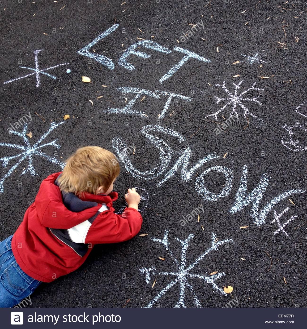 Junge liegend auf Asphalt, zeichnen mit Kreide Stockbild