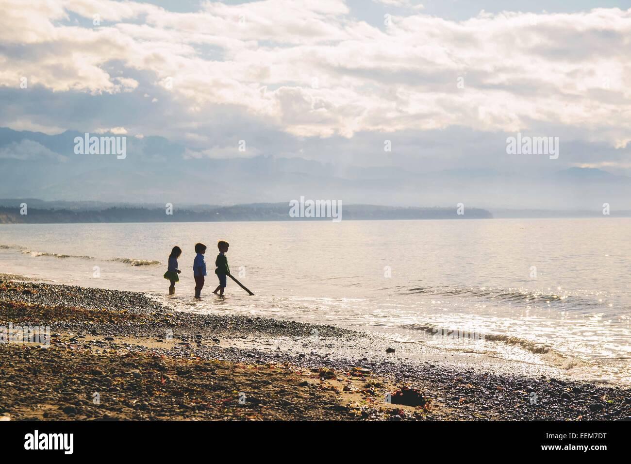 Silhouette von drei Kindern, die knöcheltief im Wasser am Strand stehen, USA Stockfoto
