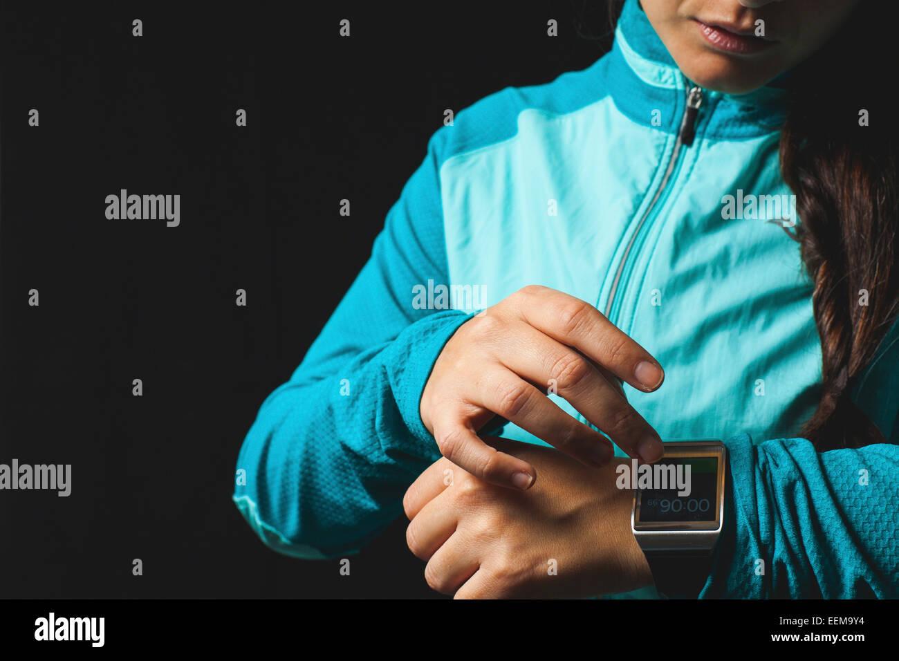 Frau trägt Smartwatch Gerät auf schwarzem Hintergrund Stockbild
