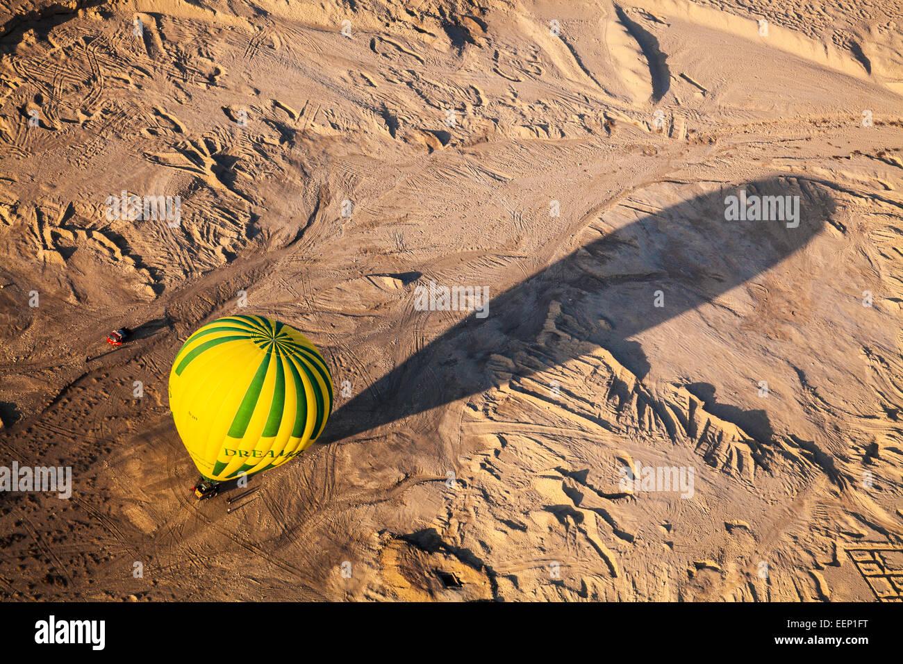Ein Heißluftballon wirft einen langen Schatten, wie es in der Wüste am Westufer des Nils in Ägypten Stockbild