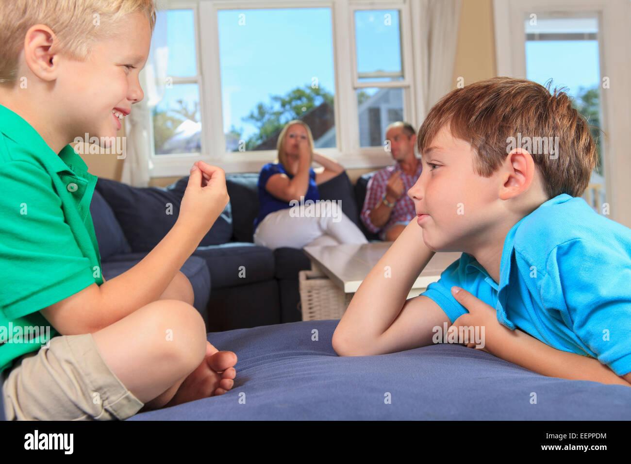 Jungen mit Hörschädigungen Unterzeichnung in amerikanischer Gebärdensprache auf ihrer Couch mit Eltern im Hintergrund Stockfoto