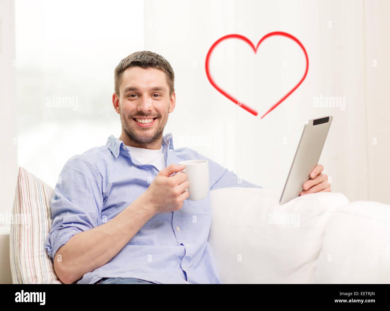 lächelnder Mann mit Tablet pc zu Hause arbeiten Stockfoto