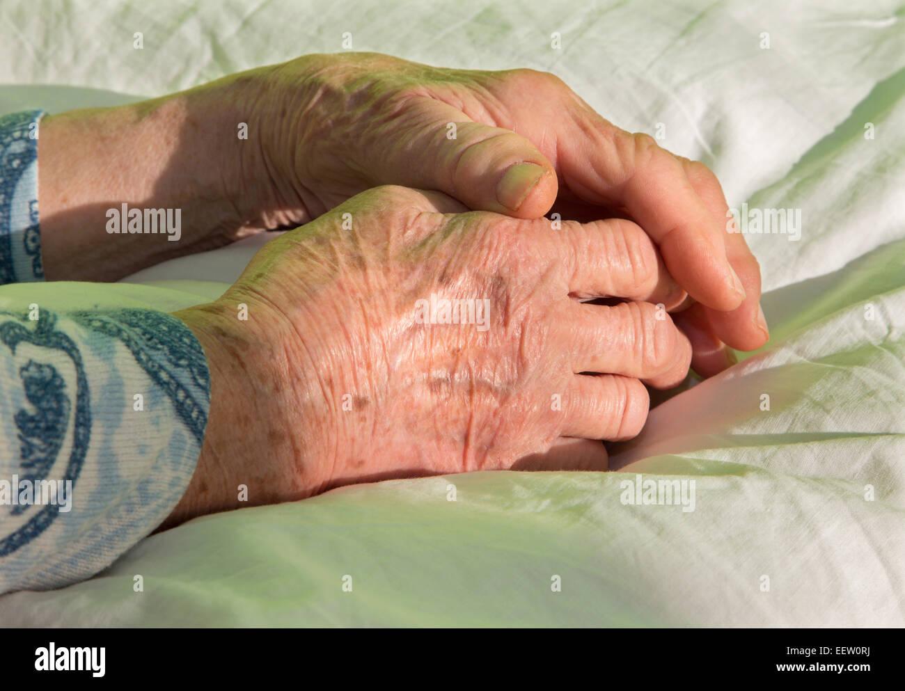 Händen der alten Frau auf dem Bett Stockbild