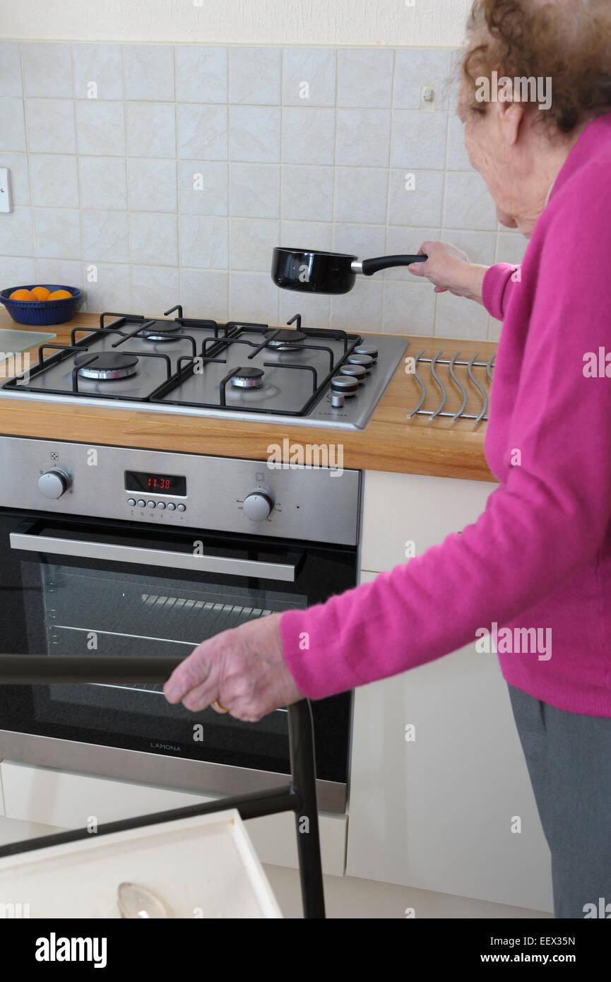 ältere Frau in ihre neunziger Jahre in einer Hand zu Fuß Halterahmen und Gas-Kochfeld mit der anderen Stockbild