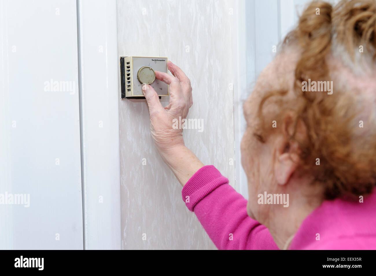 Ältere Frau in ihre neunziger Jahre einstellen, drehen Sie die Zentralheizung Thermostat in ihrem Haus, an Stockbild
