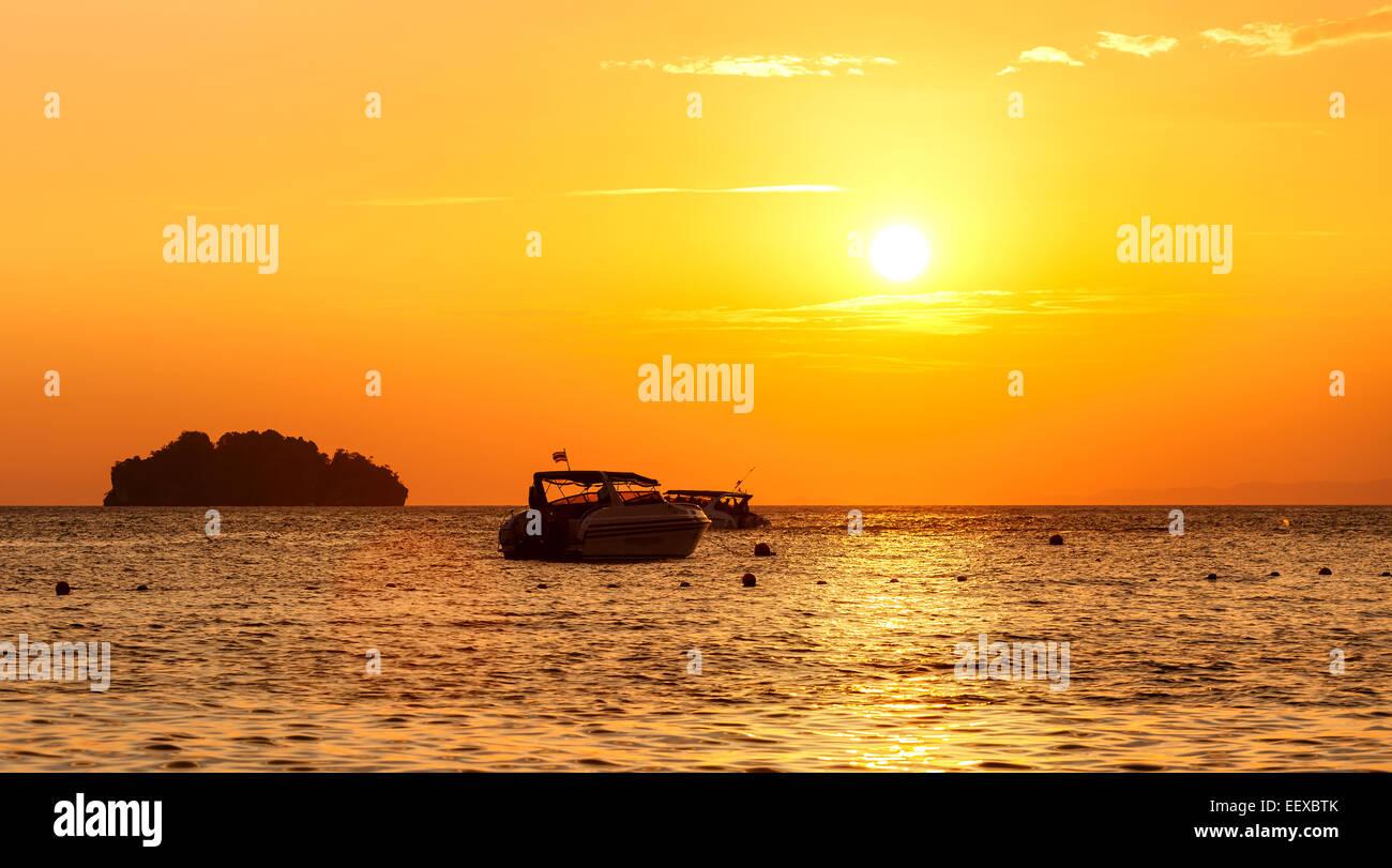 Silhouette eine kleine Insel und kleinen Boot bei Sonnenuntergang. Stockbild