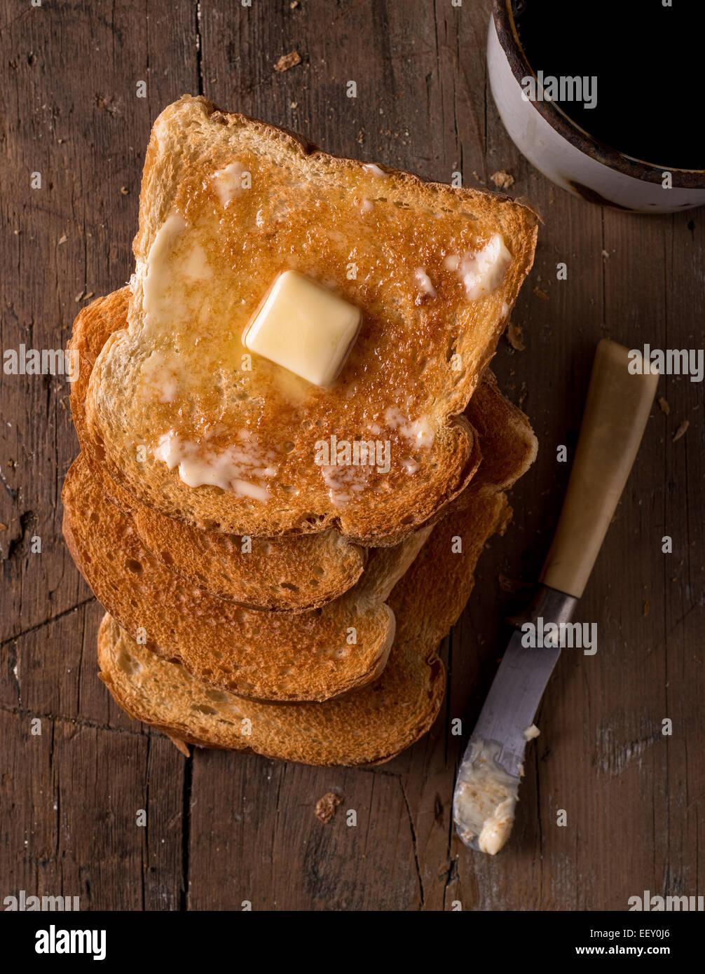Knusprigem Toast mit Butter Scheiben auf einem rustikalen Tisch mit Kaffee. Stockbild