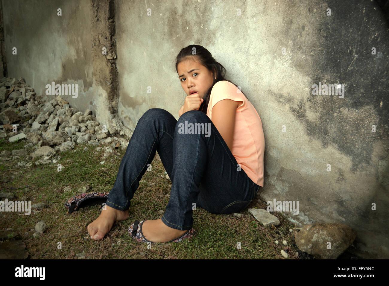 Asiatische junge Dame stützte sich auf eine Wand in einer armen Gegend betrachten etwas mit Angst vor Angst Stockbild