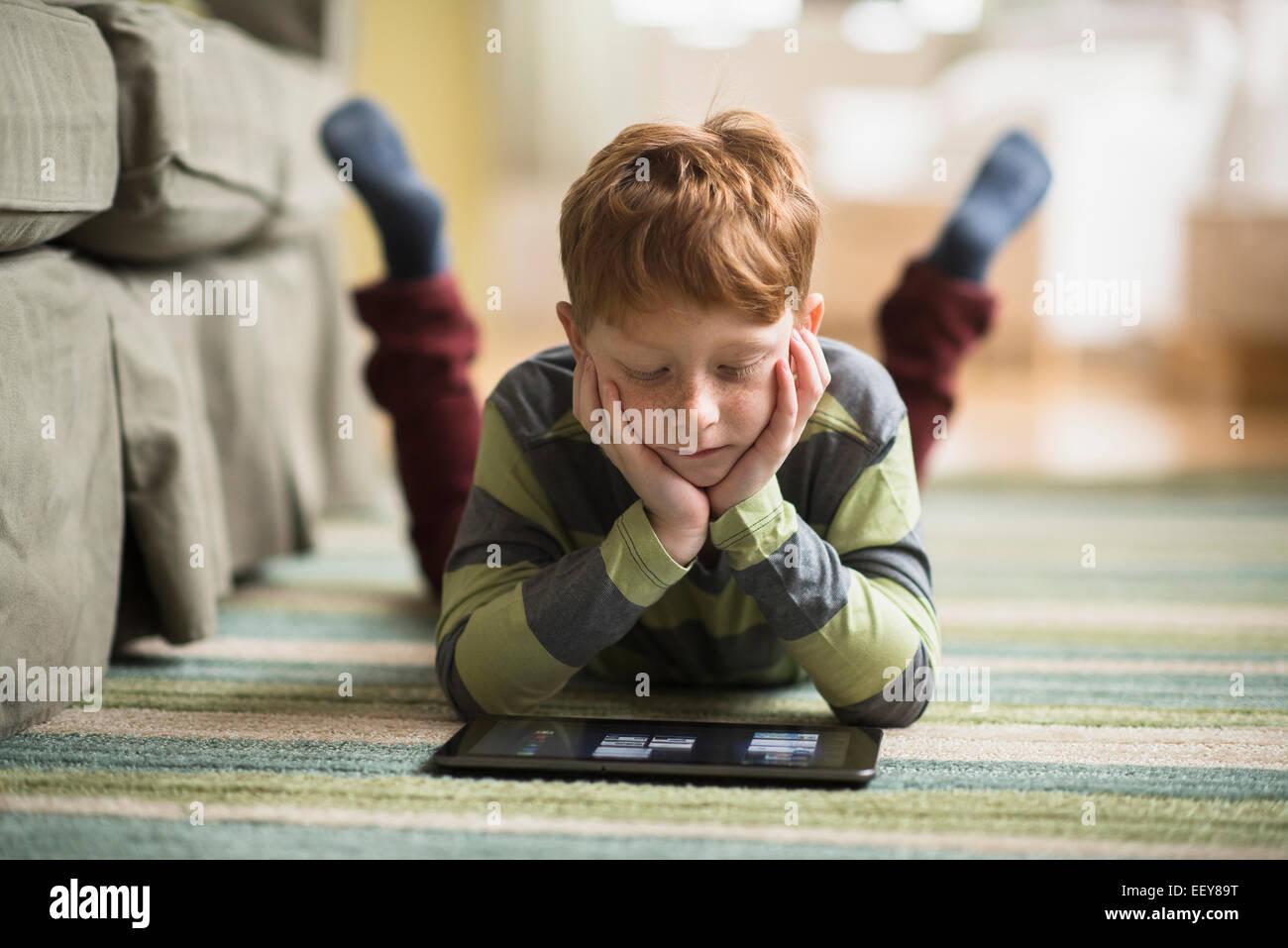 Junge (6-7) auf Teppich liegend und mit TabletPC Stockfoto