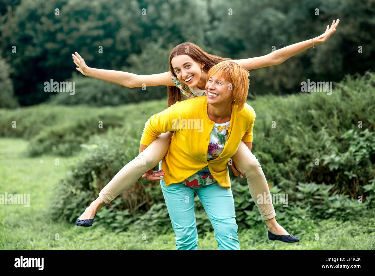 Mutter, Huckepack Reiten, ihre Tochter im park Stockbild