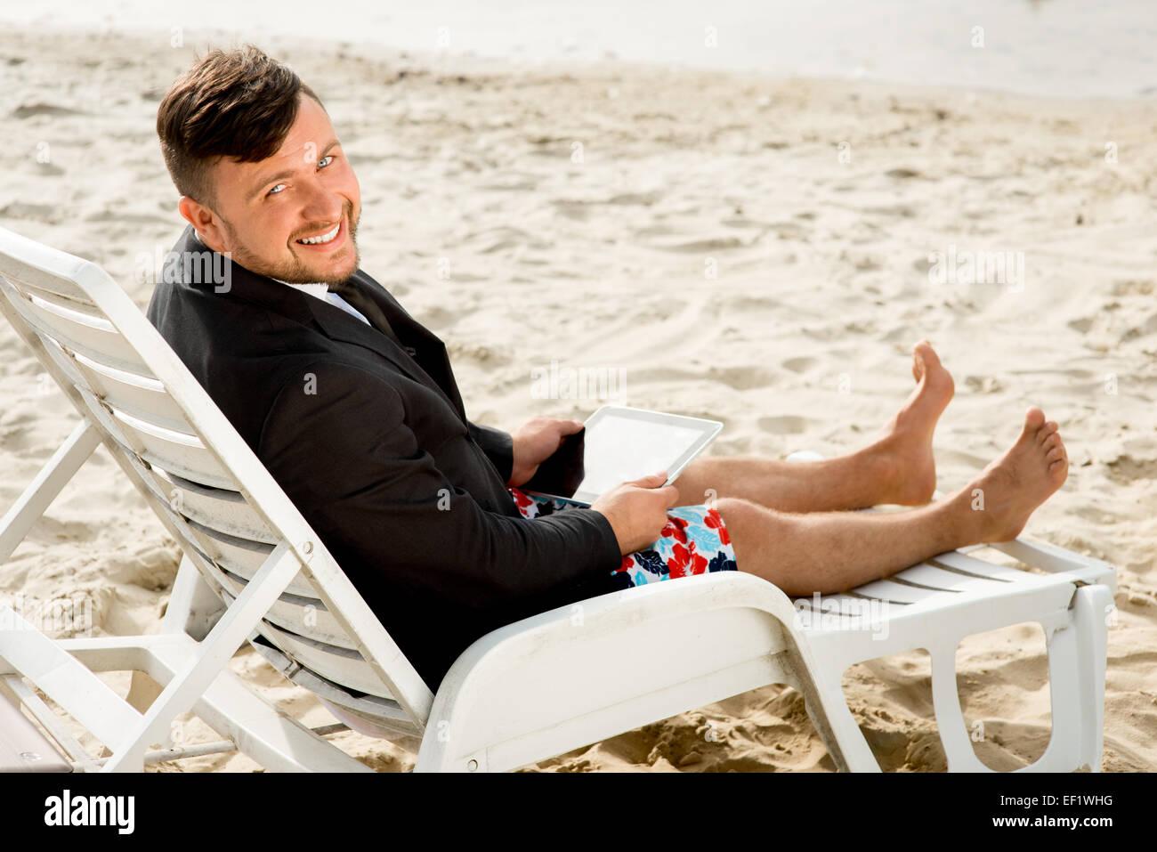gesch ftsmann gekleidet in anzug und shorts arbeiten mit laptop auf dem liegestuhl am strand. Black Bedroom Furniture Sets. Home Design Ideas