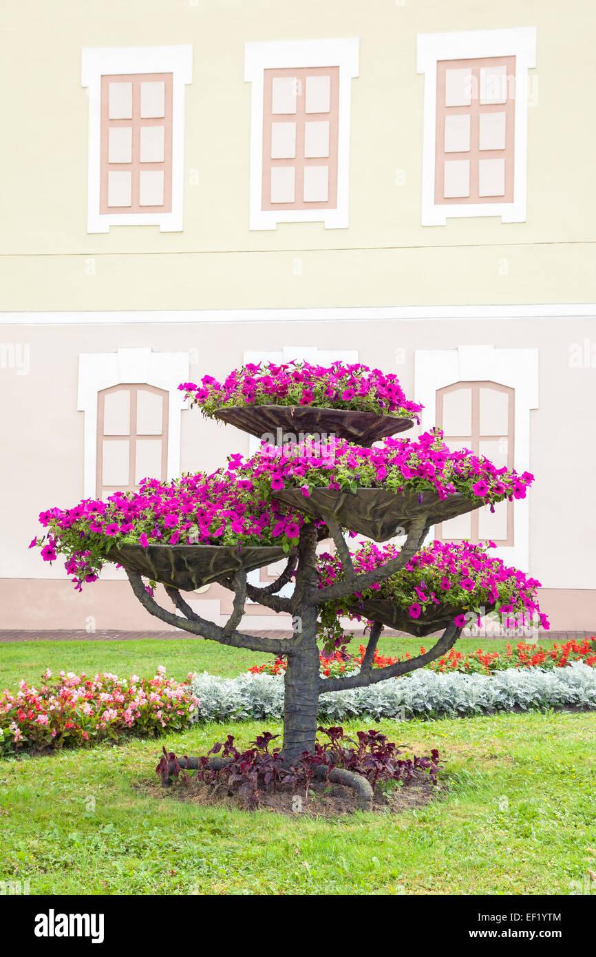 Stadt-Landschaft-Design. Blumentöpfe mit Petunia auf Baum und Blumenbeet. Stockbild