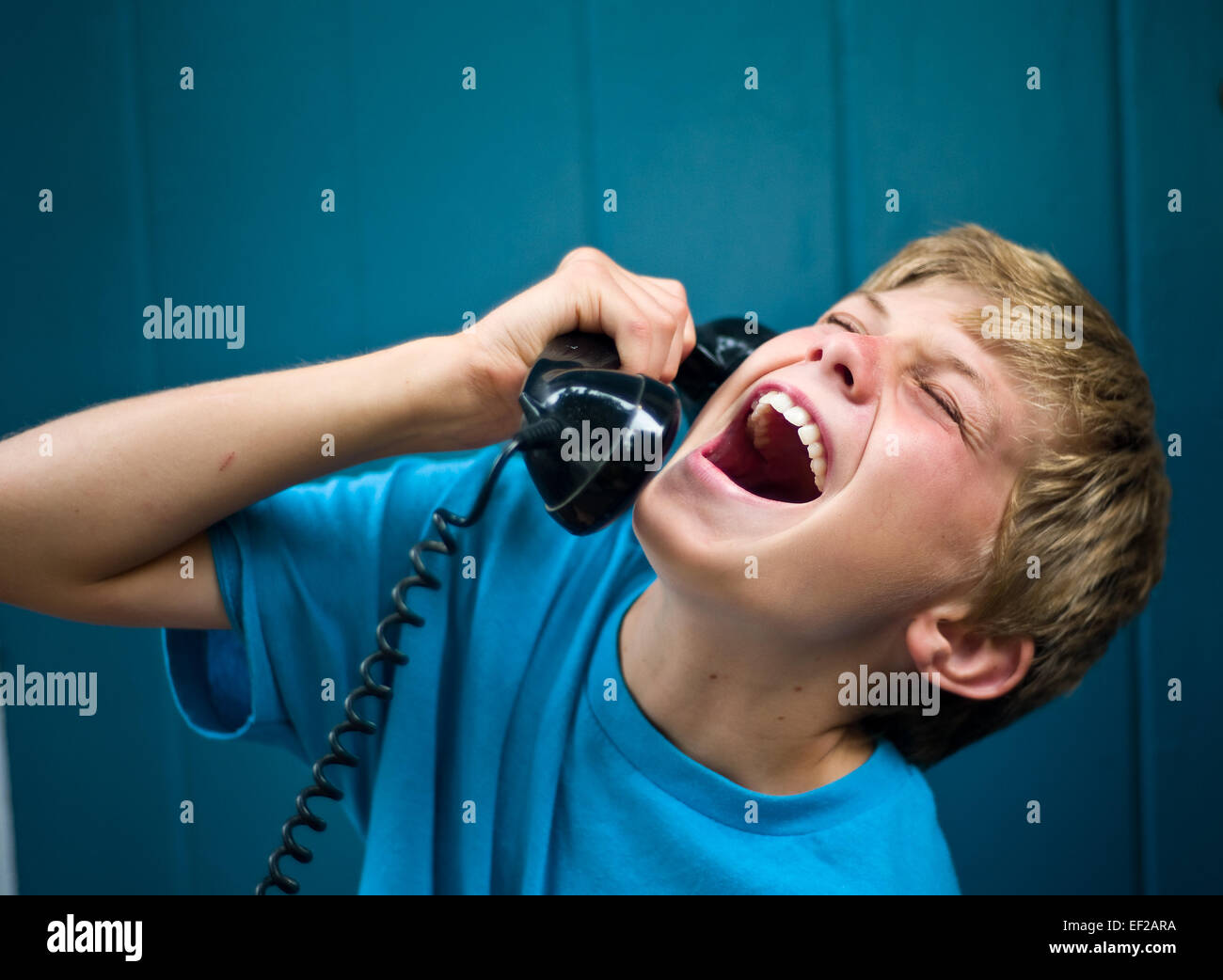 Kind 10,11,12,13 lachen während des Gesprächs am Telefon, hält Empfänger Stockfoto