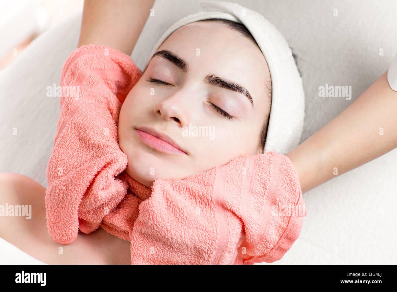 Junge Frau Gesichtsbehandlung oder Massage mit Handtuch Stockbild