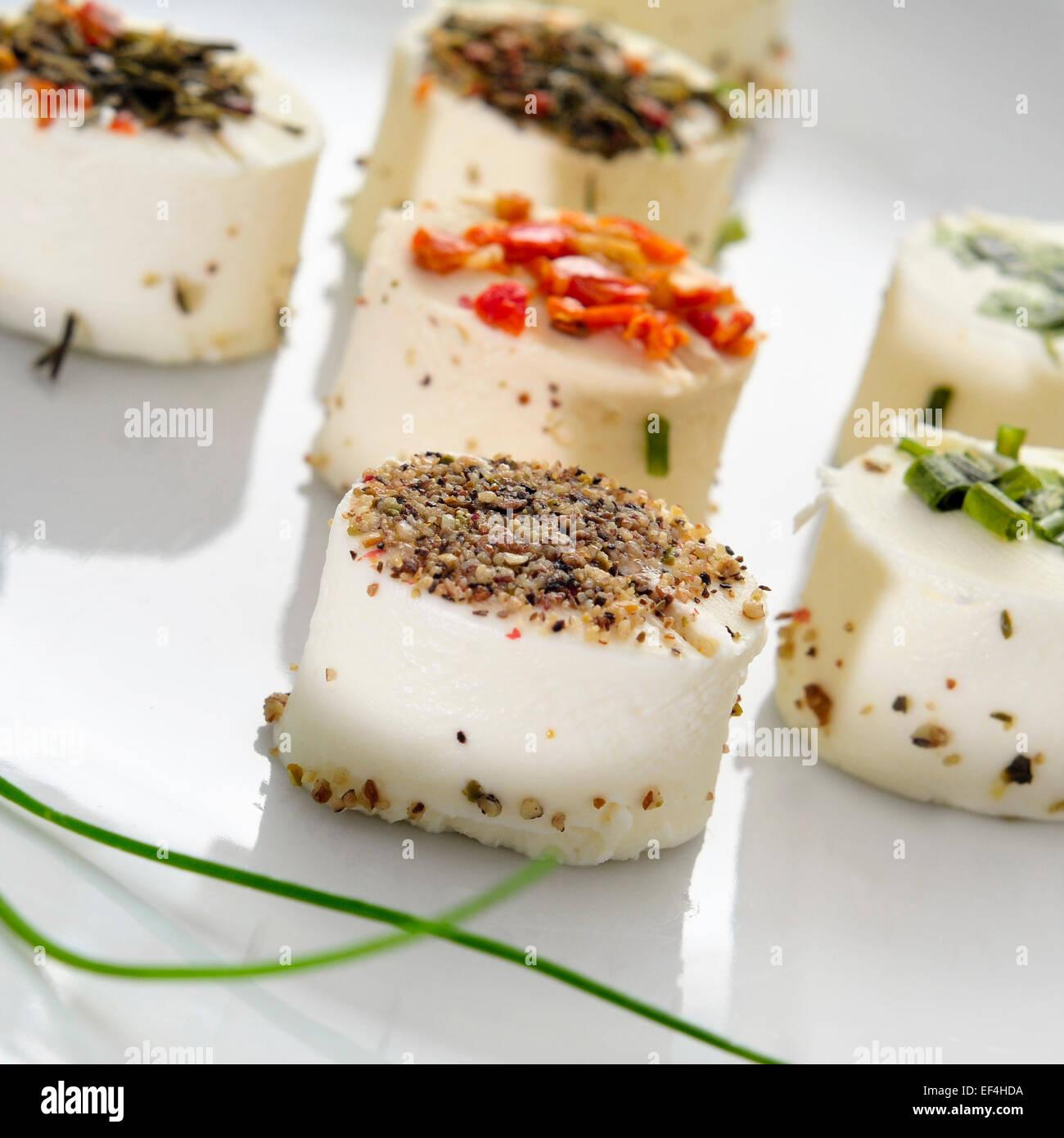 eine Platte mit einigen verschiedenen Käse-Häppchen garniert mit verschiedenen Gewürzen Stockbild