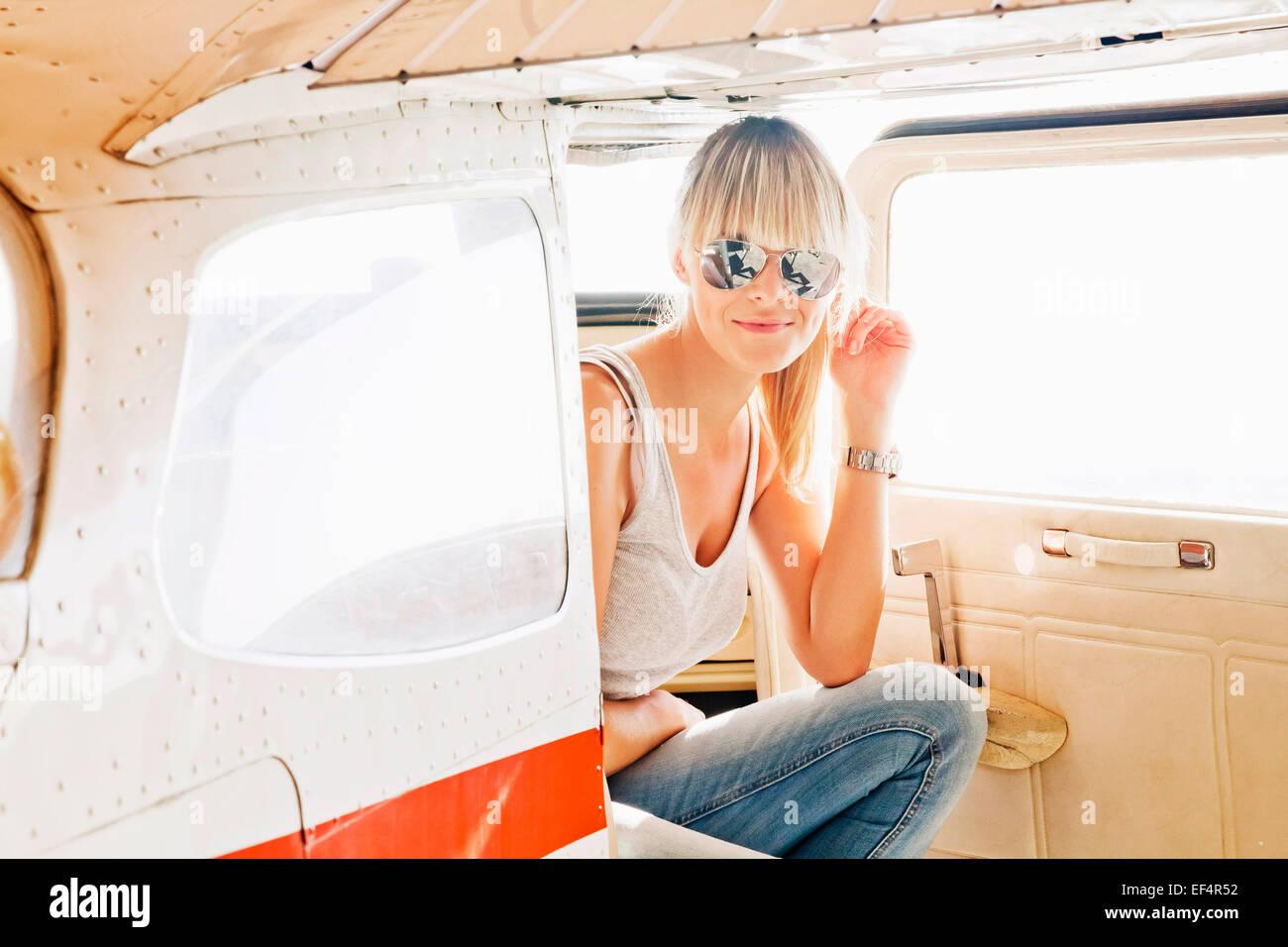 Junge Frau sitzt in einem Privatflugzeug Stockbild
