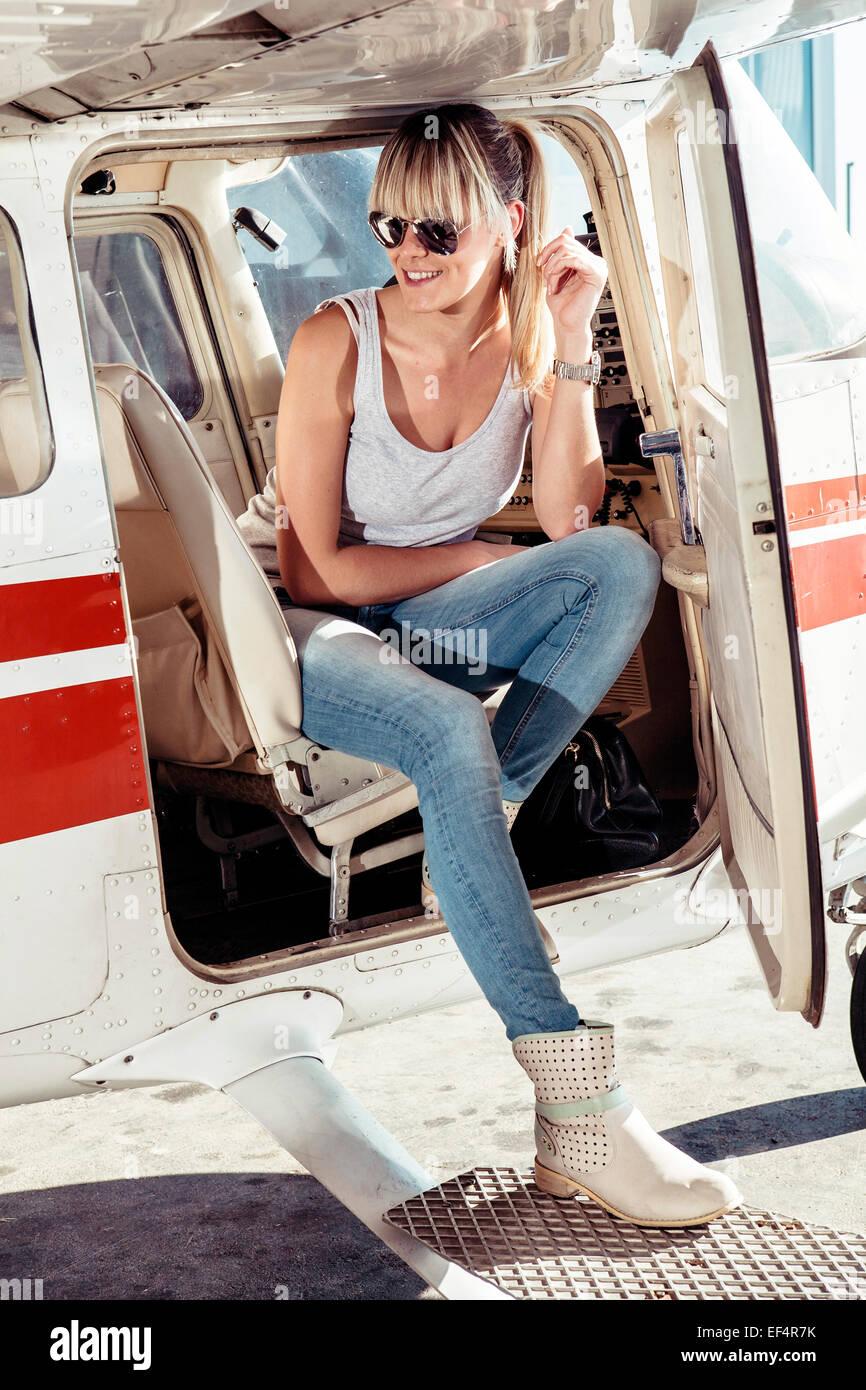 Junge Frau sitzt im Cockpit der Propellerflugzeug Stockbild