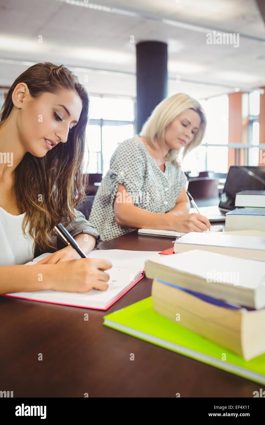 Reift Weibchen Studenten schreiben von Notizen am Schreibtisch ...