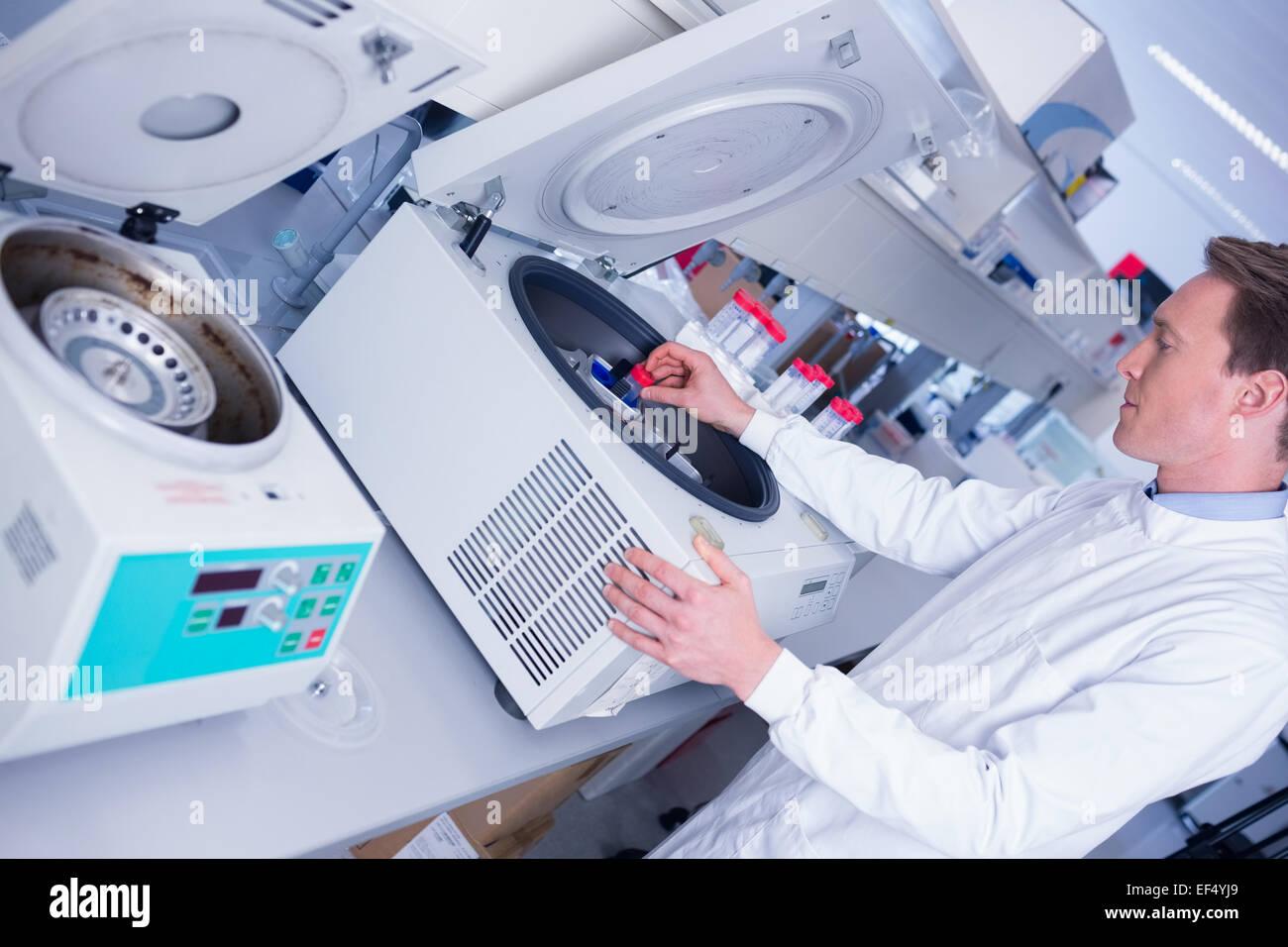 Chemiker im Laborkittel mit Hilfe einer Zentrifuge Stockbild